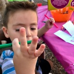 Showing me the marker that he got on his hands